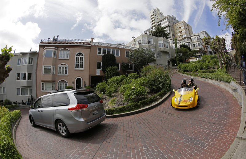 Cars make their way down Lombard Street in San Francisco, Monday, April 15, 2019. Thousands of tourists may soon have to pay as much as $10 to drive down the world-famous crooked street if a proposal announced Monday becomes law. (AP Photo/Eric Risberg)