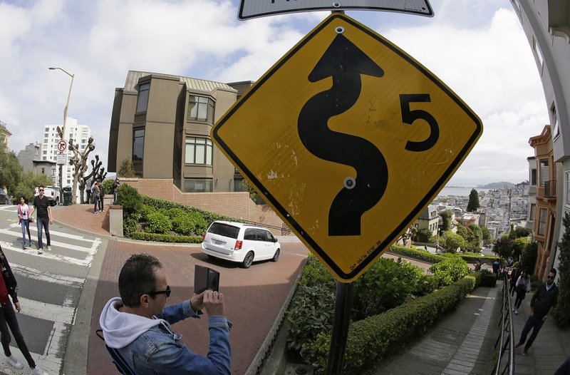 A man takes pictures as cars wind their way down Lombard Street in San Francisco, Monday, April 15, 2019. (AP Photo/Eric Risberg)