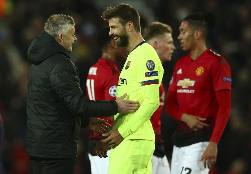 Manchester United coach Ole Gunnar Solskjaer, left, talks with Barcelona's Gerard Pique at the end of the Champions League quarterfinal, first leg, soccer match between Manchester United and FC Barcelona at Old Trafford stadium in Manchester, England, Wednesday, April 10, 2019. (AP Photo/Dave Thompson)