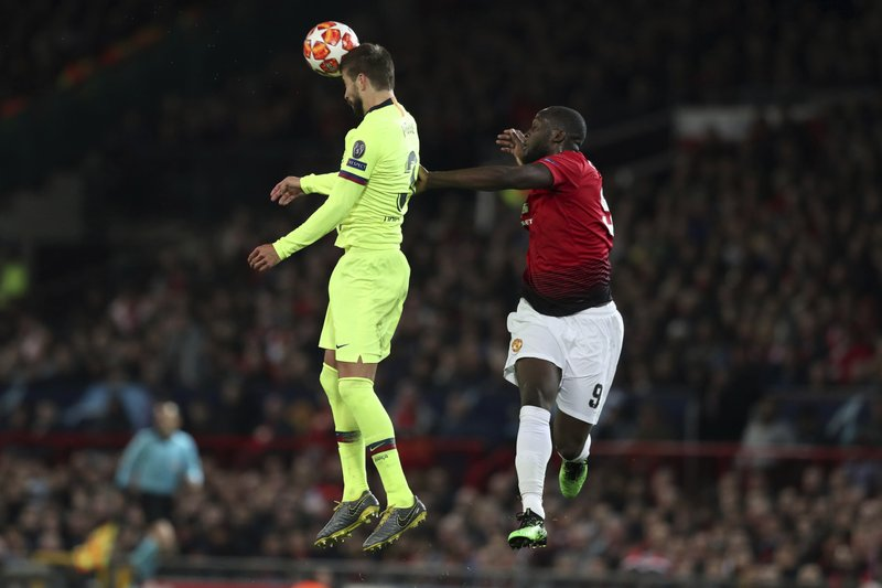 Barcelona's Gerard Pique, left, and Manchester United's Romelu Lukaku jump for the ball during the Champions League quarterfinal, first leg, soccer match between Manchester United and FC Barcelona at Old Trafford stadium in Manchester, England, Wednesday, April 10, 2019. (AP Photo/Jon Super)