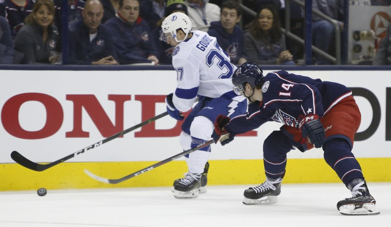 Tampa Bay Lightning's Yanni Gourde, left, carries the puck upice against Columbus Blue Jackets' Dean Kukan, of Switzerland, during the first period of Game 3 of an NHL hockey first-round playoff series Sunday, April 14, 2019, in Columbus, Ohio. (AP Photo/Jay LaPrete)