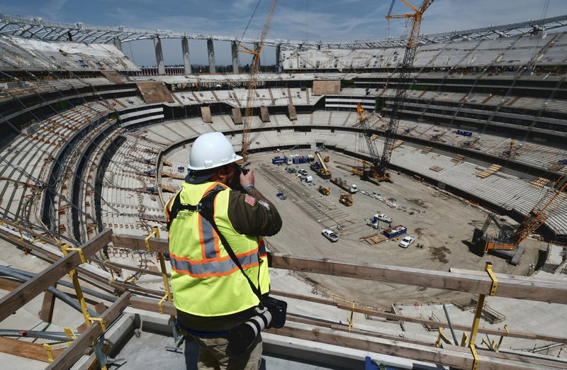 A photographer takes a photo of the new NFL Los Angeles Stadium while under construction during a topping-out ceremony in Inglewood, Calif. (AP Photo/Richard Vogel)