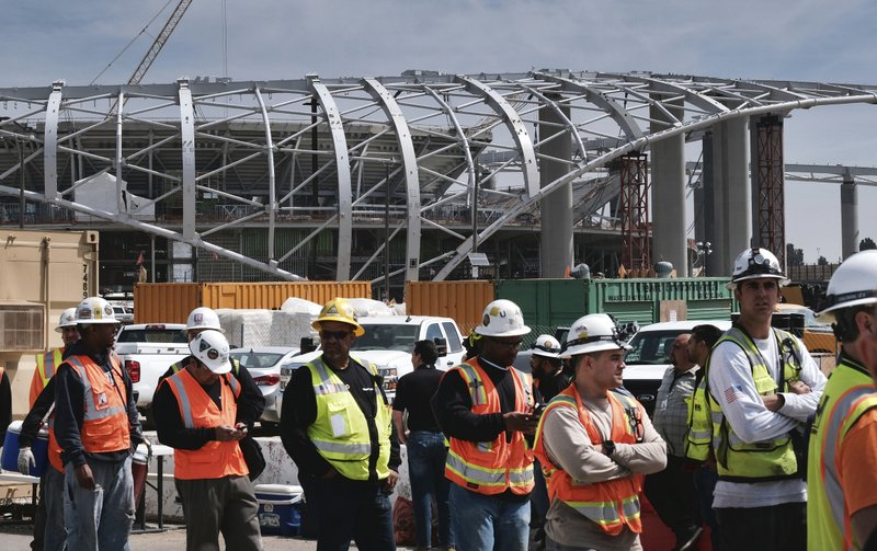 Construction workers arrive for lunch prior to an LA football stadium topping-out ceremony in Inglewood, Calif. (AP Photo/Richard Vogel)