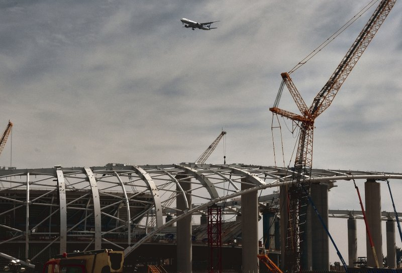 A commercial airliner makes a decent into Los Angeles International Airport over the new NFL Los Angeles Stadium under construction in Inglewood, Calif. (AP Photo/Richard Vogel)