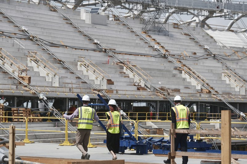 Members of the media take a tour of the new NFL Los Angeles Stadium while under construction during a topping-out ceremony in Inglewood, Calif. (AP Photo/Richard Vogel)