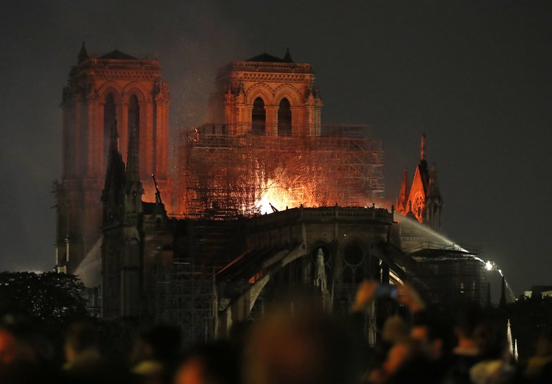 Firefighters tackle the blaze as flames and smoke rise from Notre Dame cathedral as it burns in Paris, Monday, April 15, 2019. (AP Photo/Thibault Camus)