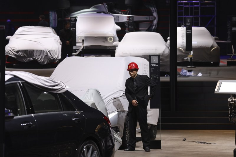 A worker stands near covered vehicles in a hall of the Auto Shanghai 2019 show in Shanghai on Monday, April 15, 2019. (AP Photo/Ng Han Guan)
