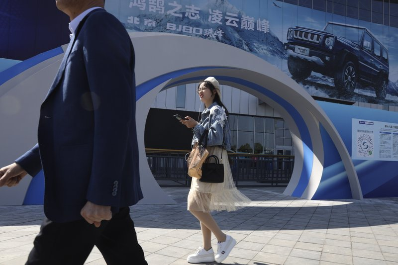 A woman walks past the entrance to the Auto Shanghai 2019 show in Shanghai on Monday, April 15, 2019. (AP Photo/Ng Han Guan)