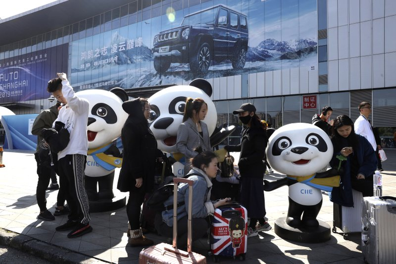 Workers wait to enter the venue for the Auto Shanghai 2019 show in Shanghai on Monday, April 15, 2019. (AP Photo/Ng Han Guan)