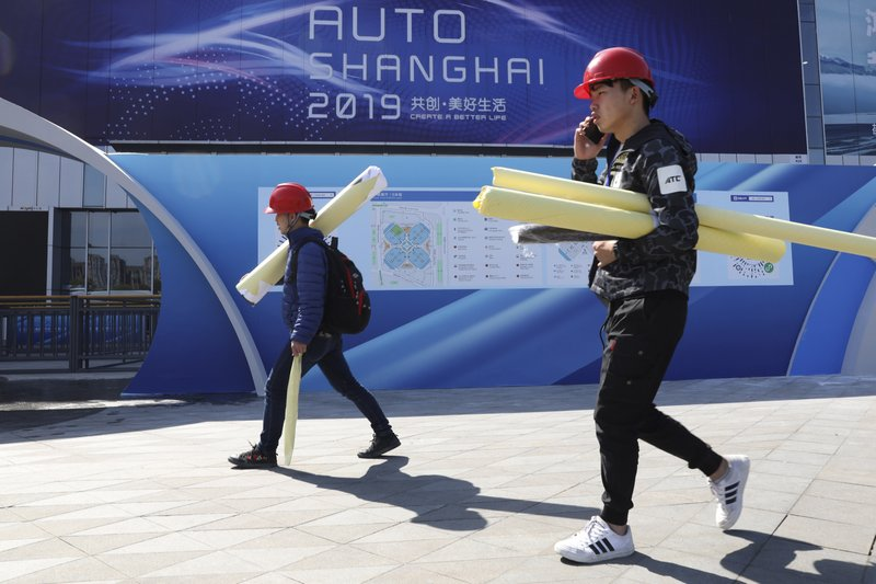 Workers prepare for the start of the Auto Shanghai 2019 show in Shanghai on Monday, April 15, 2019. This year's Shanghai auto show which starts Thursday highlights the global industry's race to make electric cars Chinese drivers want to buy as Beijing winds down subsidies that promoted sales. (AP Photo/Ng Han Guan)