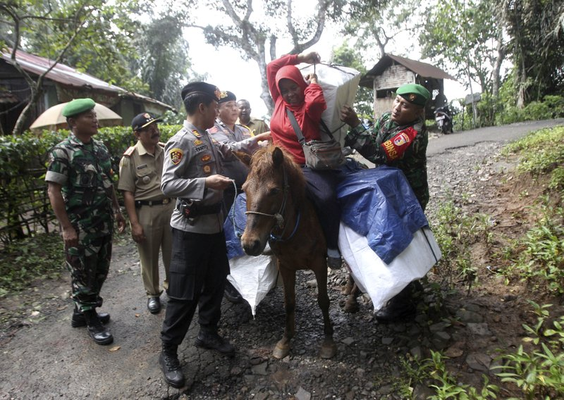 Police officers and soldiers assist a worker to carry ballot boxes and other election paraphernalia as they use horses to distribute them to polling stations in remote villages in Tempurejo, East Java, Indonesia, Monday, April 15, 2019. (AP Photo/Trisnadi)