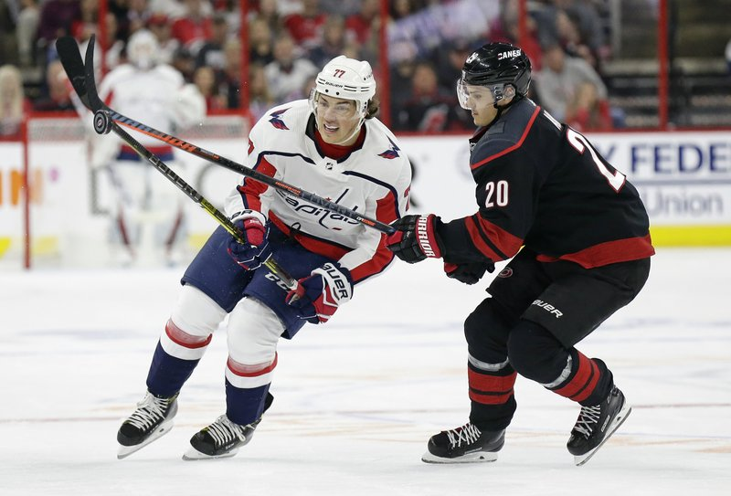 Carolina Hurricanes' Sebastian Aho (20), of Finland, and Washington Capitals' T.J. Oshie (77) chase the puck during the first period of Game 3 of an NHL hockey first-round playoff series in Raleigh, N. (AP Photo/Gerry Broome)