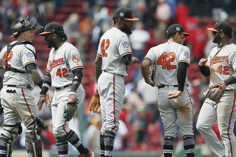 Baltimore Orioles' Miguel Castro, center, and Jesus Sucre, left, celebrate with teammates after defeating the Boston Red Sox during a baseball game in Boston, Monday, April 15, 2019. (42) in honor of Jackie Robinson Day.(AP Photo/Michael Dwyer)