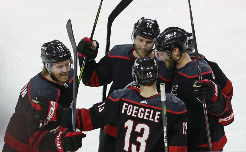 Carolina Hurricanes' Dougie Hamilton (19), Warren Foegele (13), Jordan Staal, right, and Jaccob Slavin (74) celebrate Hamilton's goal against the Washington Capitals during the third period of Game 3 of an NHL hockey first-round playoff series in Raleigh, N. (AP Photo/Gerry Broome)