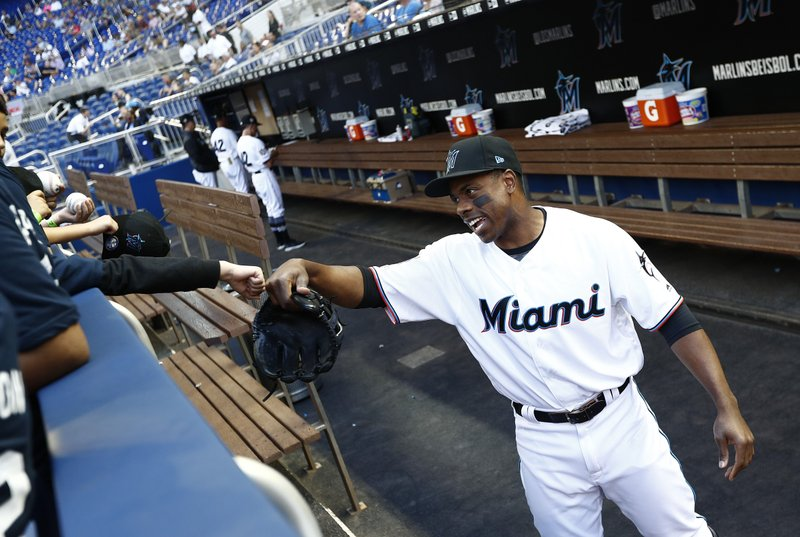 Miami Marlins left fielder Curtis Granderson laughs with a young fan before a baseball game against the Chicago Cubs, Monday, April 15, 2019, in Miami. (AP Photo/Brynn Anderson)