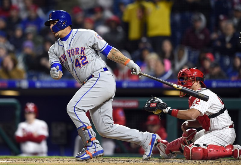New York Mets' Wilson Ramos, left, watches the ball in front of Philadelphia Phillies' J.T. Realmuto after hitting a two-run single off Aaron Nola during the third inning of a baseball game, Monday, April 15, 2019, in Philadelphia. (AP Photo/Derik Hamilton)