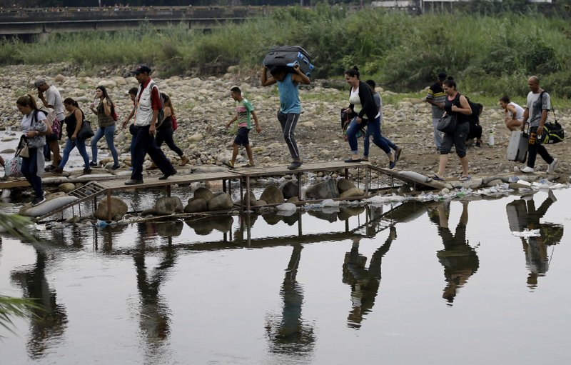 FILE - In this April 14, 2019 file photo, Venezuelans cross illegally into Colombia near the Simon Bolivar International Bridge, top, which is partially closed by Venezuelan authorities who are only permitting students, seniors and the sick to cross, seen from La Parada near Cucuta, Colombia. (AP Photo/Fernando Vergara, File)
