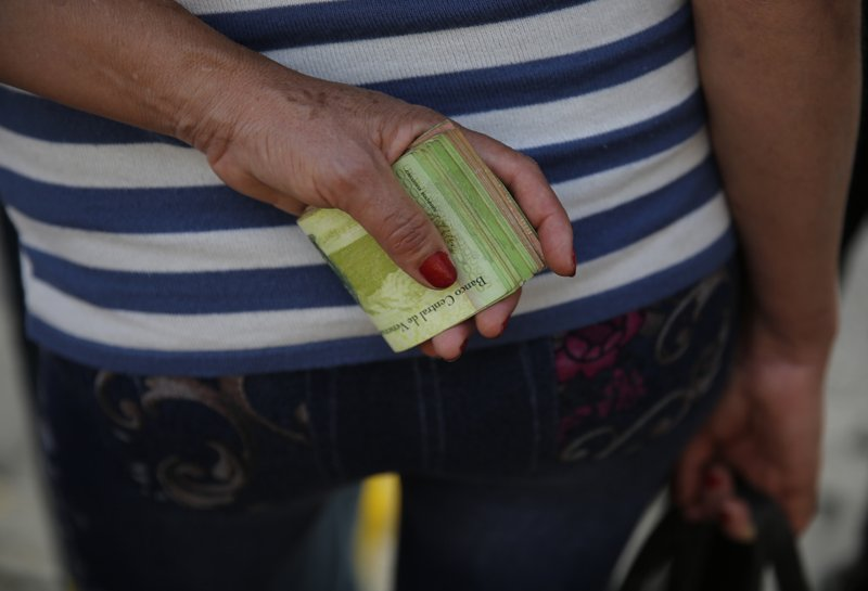 FILE - In this Feb. 7, 2018 file photo, a woman holds a large wad of bills to pay her bus fare in Caracas, Venezuela. (AP Photo/Ariana Cubillos, File)