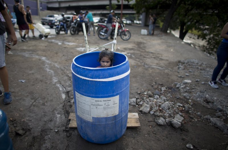FILE - In this March 11, 2019 file photo, a little girl stands inside a plastic barrel while her family waits to collect water from an open pipe above the Guaire River, during rolling blackouts which has cut people off from running water in Caracas, Venezuela. (AP Photo/Ariana Cubillos, File)