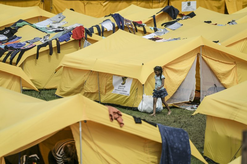 FILE - In this Nov. 21, 2018 file photo, a girl walks in a camp built by the municipal government for homeless Venezuelan migrants in Bogota, Colombia. (AP Photo/Ivan Valencia, File)