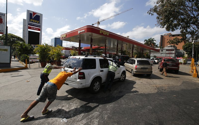 FILE - In this March 10, 2019 file photo, people push a car without fuel to one of the few gas stations that has its own electric generator during an electricity blackout in Caracas, Venezuela. (AP Photo/Eduardo Verdugo, File)