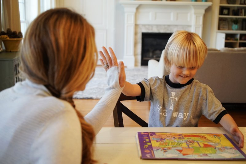 In this Wednesday, March 27, 2019, photo, Kacey Ruegsegger Johnson high-fives with her son Corban as they finish a puzzle in their Cary, N. (AP Photo/Allen G. Breed)