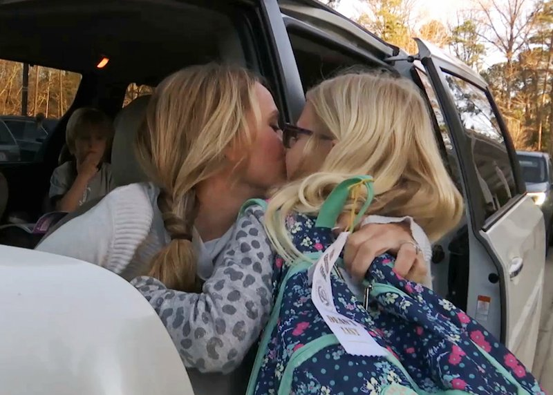 In this Wednesday, March 27, 2019, frame from video, Kacey Ruegsegger Johnson kisses her daughter, Logan, as she drops her off at her school in Cary, N. (AP Photo/Allen G. Breed)