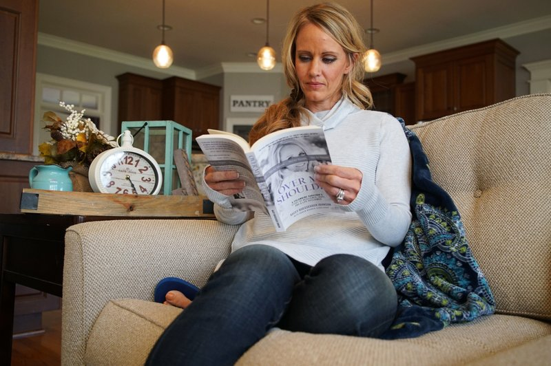 In this Wednesday, March 27, 2019, photo, Kacey Ruegsegger Johnson pages through a copy of her memoir at her home in Cary, N. (AP Photo/Allen G. Breed)