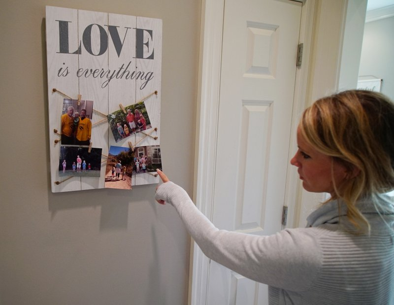 In this Wednesday, March 27, 2019, photo, Kacey Ruegsegger Johnson looks at photos of her family at her home in Cary, N. (AP Photo/Allen G. Breed)