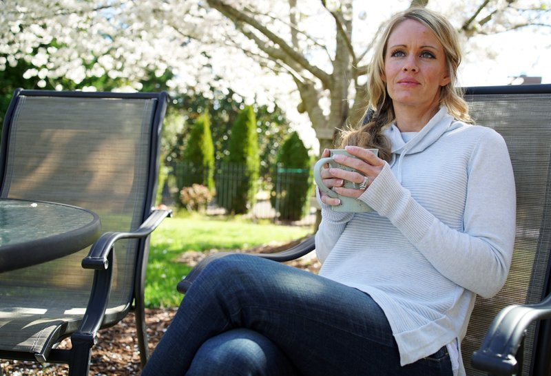 In this Wednesday, March 27, 2019, photo, Kacey Ruegsegger Johnson enjoys a coffee in a light spring breeze in the back yard of her home in Cary, N. (AP Photo/Allen G. Breed)