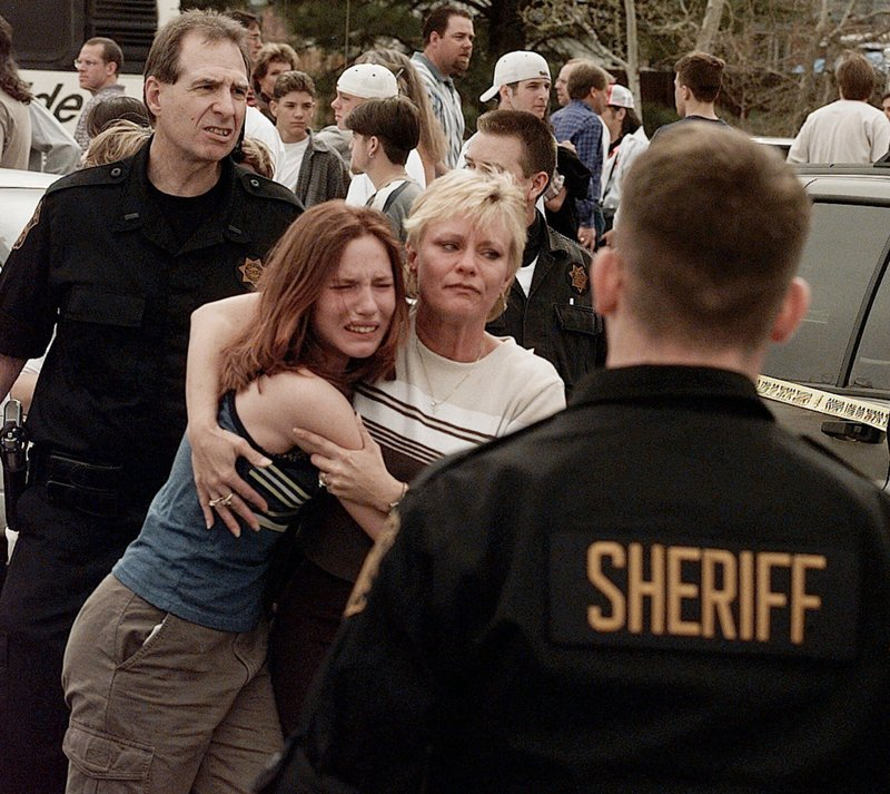 FILE - In this April, 20, 1999, file photo, a woman embraces her daughter after they were reunited following a shooting at Columbine High School in Littleton, Colo. (AP Photo/Ed Andrieski, File)