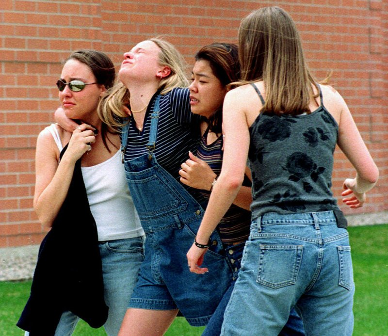 FILE - In this April 20, 1999, file photo, women head to a library near Columbine High School where students and faculty members were evacuated after two gunmen went on a shooting rampage in the school in the Denver suburb of Littleton, Colo. (AP Photo/Kevin Higley, File)