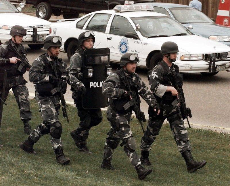 FILE - In this April 20, 1999, file photo, members of a police SWAT team march to Columbine High School in Littleton, Colo. (AP Photo/Ed Andrieski, File)