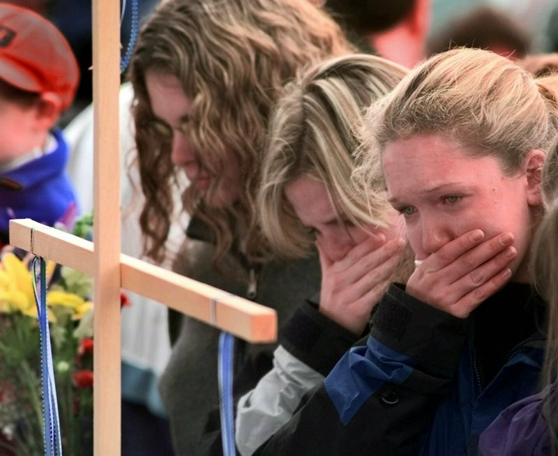 FILE - In this April 22, 1999, file photo, Columbine High School students, from left, Darcy Craig, Molly Byrne and Emily Dubin stop to pay their respects at a makeshift memorial set up in a park near the high school in Littleton, Colo. (AP Photo/Eric Gay, File)
