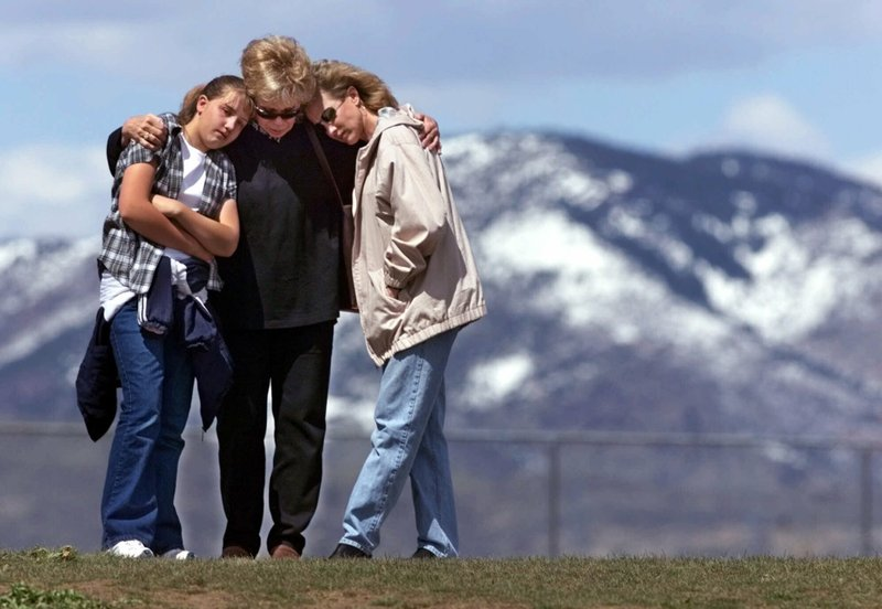 FILE - In this April 27, 1999, file photo, Krista Sleeth, Bev Fleer and Cindy Sleeth embrace while standing on a hill above Columbine High School in Littleton, Colo. (AP Photo/Michael S. Green, File)