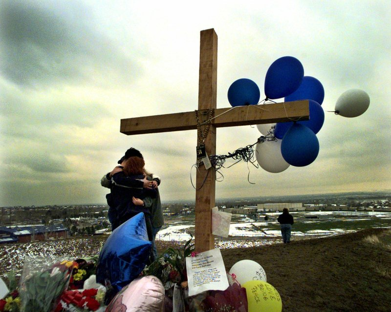 FILE - In this April 24, 1999, file photo, students embrace each other at a makeshift memorial for their slain classmates at Columbine High School on a hilltop overlooking the school in Littleton, Colo. (AP Photo/Bebeto Matthews, File)
