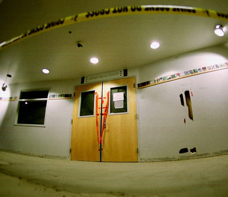 FILE - In this June 15, 1999, file photo, tape marks the line in front of the doors to the library in Columbine High School as members of the media took their first trip through the school in the southwest Denver suburb of Littleton, Colo. (AP Photo/David Zalubowski, File)