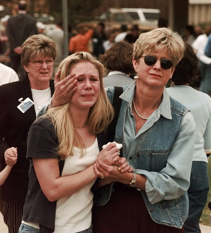 FILE - In this April 20, 1999, file photo, Fran Allison, right, comforts her daughter Brooke after they were reunited after a shooting at Columbine High School in Denver. (AP Photo/Ed Andrieski, File)