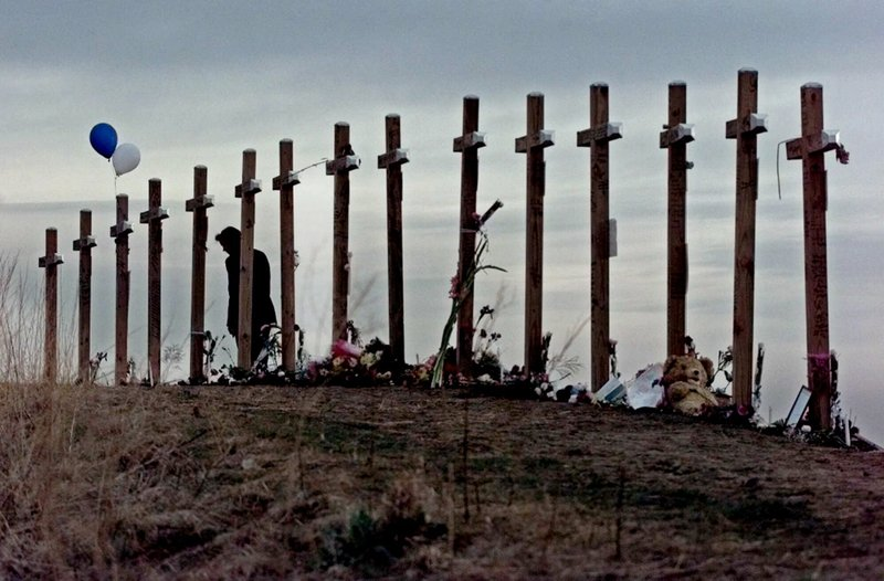 FILE - In this April 28, 1999, file photo, a woman looks at crosses posted on a hill above Columbine High School in Littleton, Colo. (AP Photo/Eric Gay, File)