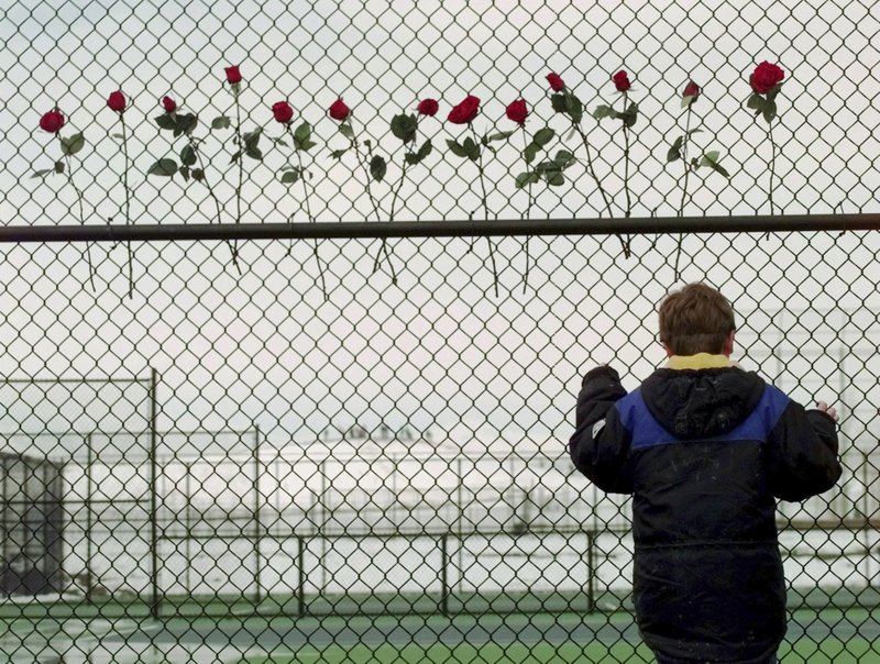 FILE - In this April 24, 1999, file photo, a boy looks through the fence at the Columbine High School tennis courts in Littleton, Colo. (AP Photo/Eric Gay, File)