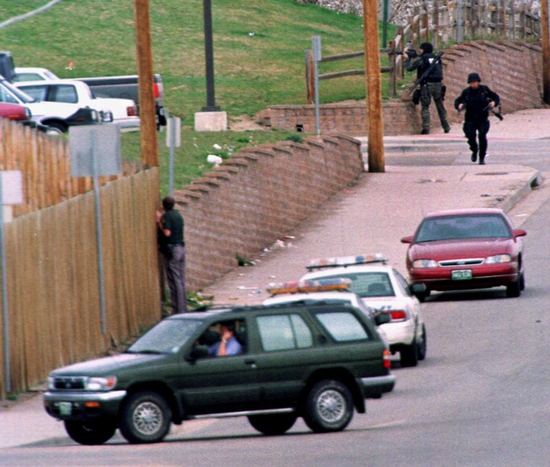 FILE - In this April 20, 1999, file photo, SWAT members run down Pierce Street while a Jefferson County, Colo. (AP Photo/David Zalubowski, File)