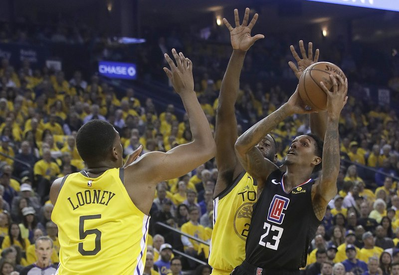 Los Angeles Clippers guard Lou Williams (23) shoots against Golden State Warriors center Kevon Looney (5) and forward Draymond Green during the first half of Game 2 of a first-round NBA basketball playoff series in Oakland, Calif. (AP Photo/Jeff Chiu)