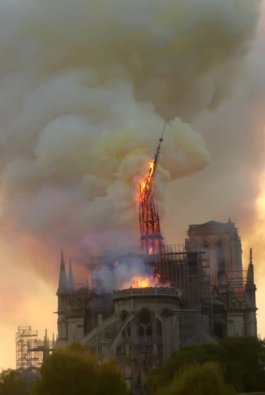 Flames and smoke rise as the spire of Notre Dame cathedral collapses in Paris, Monday, April 15, 2019. (AP Photo/Dominique Bichon)