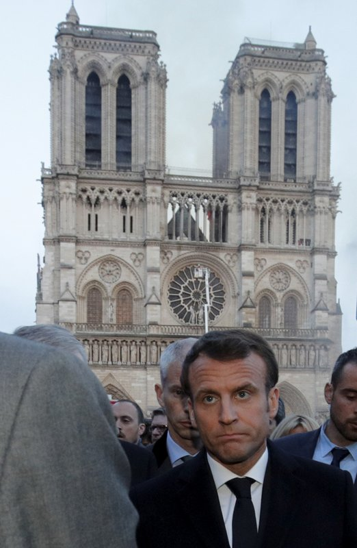 French President Emmanuel Macron walks by Notre Dame Cathedral during his visit to the site in Paris, Monday, April 15, 2019. (Philippe Wojazer/Pool via AP)