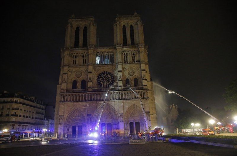 Firefighters spray water onto the facade of Notre Dame cathedral to stop the spread of a fire in Paris, Monday, April 15, 2019. (AP Photo/Michel Euler)