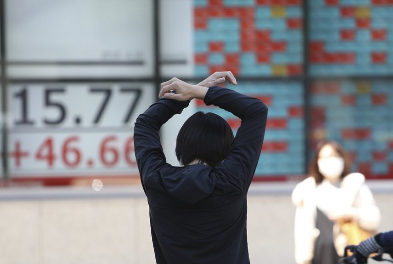A man stretches in front of an electronic stock board of a securities firm in Tokyo, Tuesday, April 16, 2019. (AP Photo/Koji Sasahara)