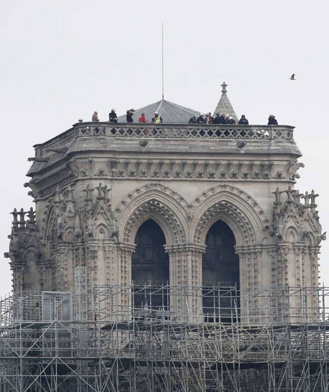Firemen inspect the Notre Dame cathedral after the fire in Paris, Tuesday, April 16, 2019. Experts are assessing the blackened shell of Paris' iconic Notre Dame cathedral to establish next steps to save what remains after a devastating fire destroyed much of the almost 900-year-old building. (AP Photo/Christophe Enaa)