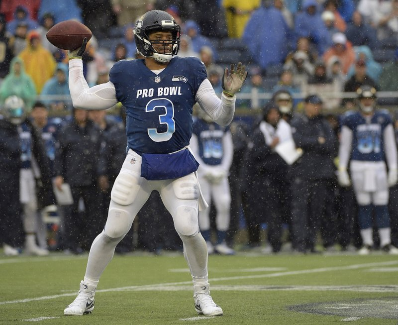 FILE - In this  Jan. 27, 2019, file photo, NFC quarterback Russell Wilson of the Seattle Seahawks throws a pass against the AFC during the first half of their NFL Pro Bowl football game in Orlando, Fla. (AP Photo/Phelan Ebenhack, File)