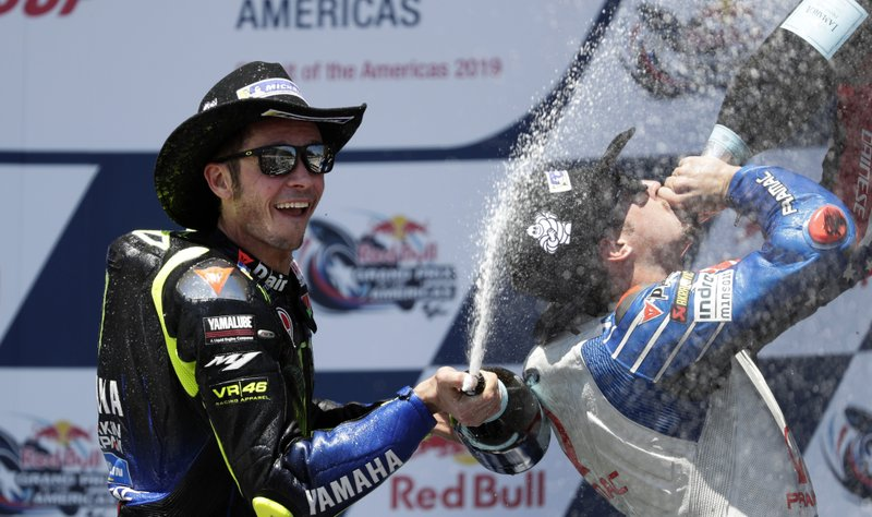 Valentino Rossi, left, of Italy, celebrates his second-place finish in the Grand Prix of the Americas motorcycle race at the Circuit of the Americas, Sunday, April 14, 2019, in Austin, Texas. (AP Photo/Eric Gay)