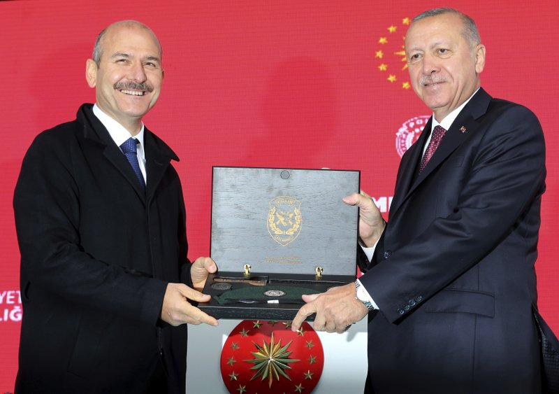 Turkey's President Recep Tayyip Erdogan, right, receives a souvenir from his Interior Minister Suleyman Soylu during a ceremony at the headquarters of a special security force in Ankara, Turkey, Wednesday, April 10, 2019. (Presidential Press Service via AP, Pool)